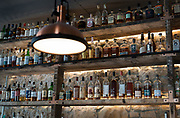 Alcohol bottles line the bar behind Boar and Barrel in Madison, WI on Thursday, May 16, 2019.