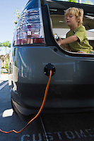 Boy (5-6) sitting in open car trunk at gas station