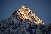 Day 3 of 10: Sunrise light strikes Nevado Taulliraju (19,100 ft or 5830 m) seen from Huaripampa Valley. Trek 10 days around Alpamayo in Huascaran National Park (UNESCO World Heritage Site), Cordillera Blanca, Andes Mountains, Peru, South America.