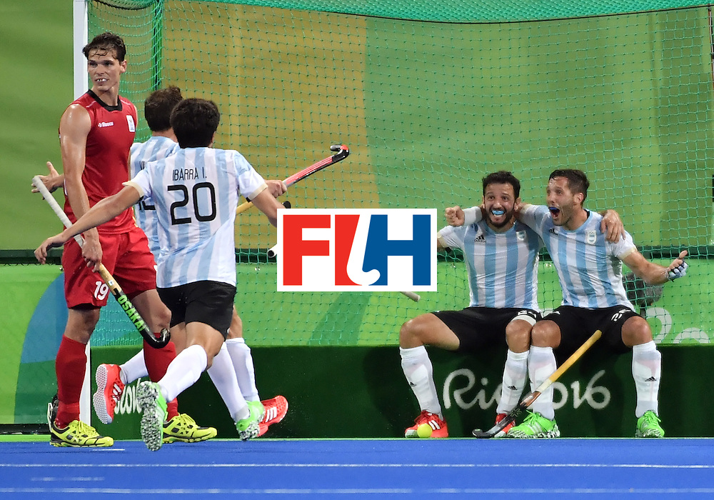 Argentina's Agustin Mazzilli (R) celebrates his goal with teammates during the men's Gold medal field hockey Belgium vs Argentina match of the Rio 2016 Olympics Games at the Olympic Hockey Centre in Rio de Janeiro on August 18, 2016. / AFP / Pascal GUYOT        (Photo credit should read PASCAL GUYOT/AFP/Getty Images)