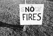 "Small wooden sign saying ""sNOw FIRES"" stand in grass.Glastonbury 1999"