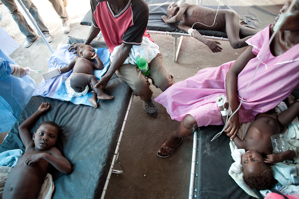 Parents sit with their children who are being treated for cholera.