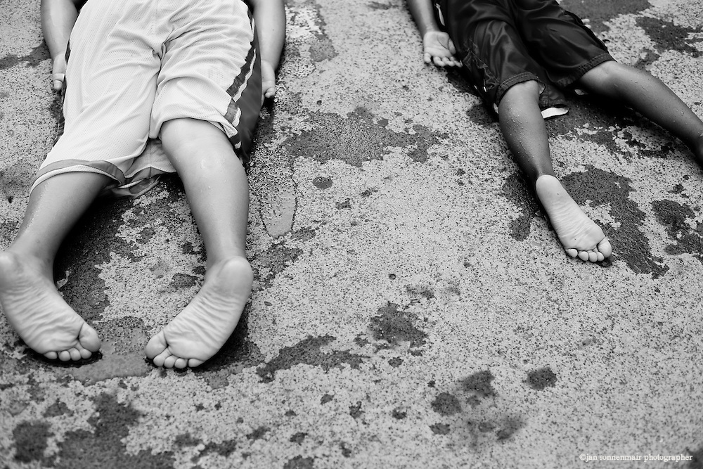 Two boys lay in wet swimsuits on the hot summer ground at Keller Fountain Park in Downtown Portland, Oregon