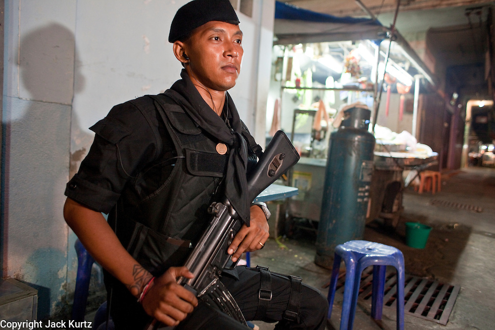 """Sept. 24, 2009 -- PATTANI, THAILAND:  A member of the Thai Rangers, a paramilitary militia trained by the Thai army guard the Pattani night market in Pattani, Thailand. Thailand's three southern most provinces; Yala, Pattani and Narathiwat are often called """"restive"""" and a decades long Muslim insurgency has gained traction recently. Nearly 4,000 people have been killed since 2004. The three southern provinces are under emergency control and there are more than 60,000 Thai military, police and paramilitary militia forces trying to keep the peace battling insurgents who favor car bombs and assassination.   Photo by Jack Kurtz"""