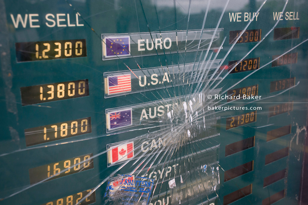 Cracked glass in a foreign currency exchange rates window.