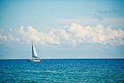 A sailboat sails across a blue ocean against a cloudy sky.