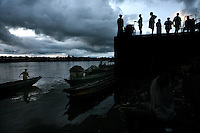 People converse on market dock just before sunset on the Atrato River in Quibdo, the capital of the state of Choco, on October 6, 2006. Choco is a state that has suffered terribly at the hands of both rightwing paramilitaries and leftist rebels over the years, causing many to flee to other parts of Colombia. The Choco is located on the Pacific coast of Colombia and most of the people are black descendants of African slaves. (Photo/Scott Dalton)