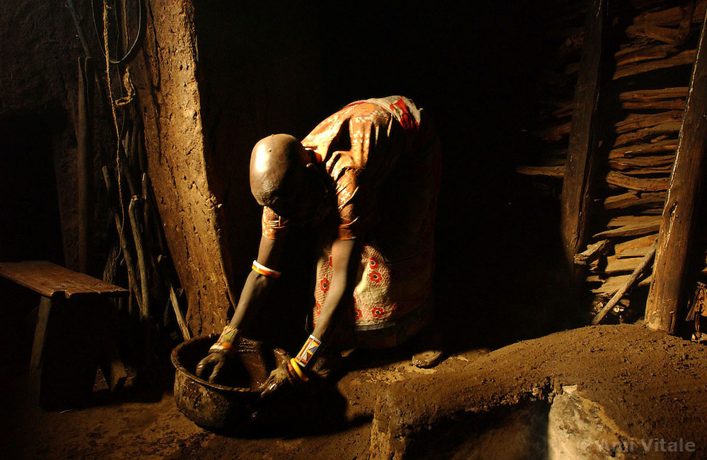 A Maasai pastoralist who participates in the Farmers Field School puts mud on the stove in her kitchen  in a village near Narok, Kenya November 4, 2003. (Photo by Ami Vitale)