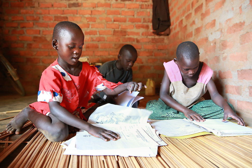CAPTION: Catherine's children, immersed in their studies at home in Kaberamaido. LOCATION: Apapai Parish, Otuboi Sub-county, Kalaki County, Kaberamaido District, Uganda. INDIVIDUAL(S) PHOTOGRAPHED: From left to right: Nancy Acen, Innocent Jacob Okot and Cecilia Acwichi.