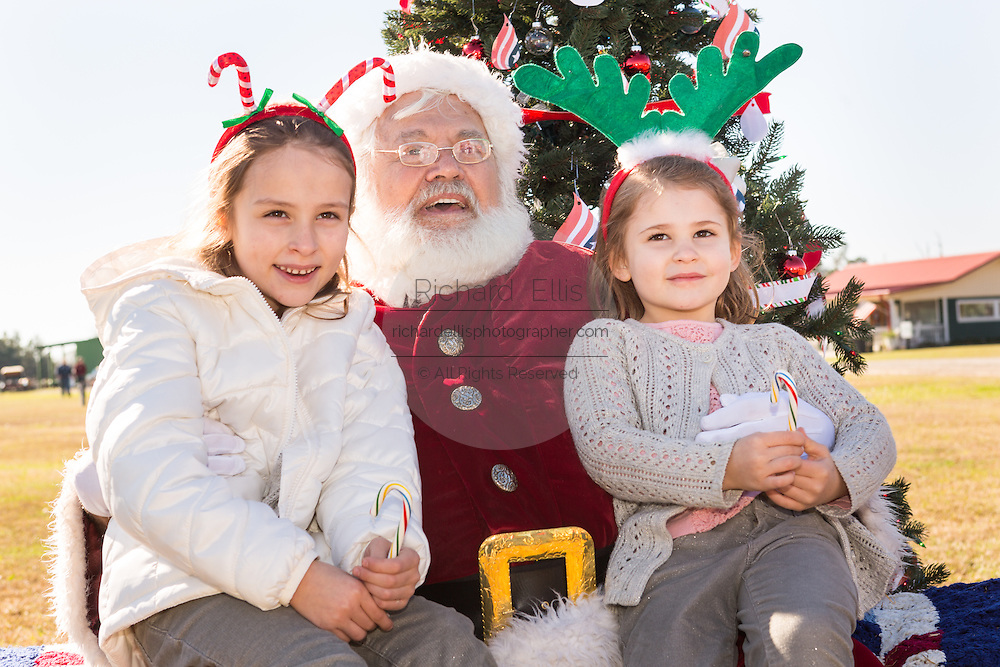 Santa Claus sits with Catherine (R) and Caroline Cruz, daughters of Senator and GOP presidential candidate Ted Cruz during a campaign event at Ottawa Farms December 19, 2015 in Bloomingdale, Georgia.