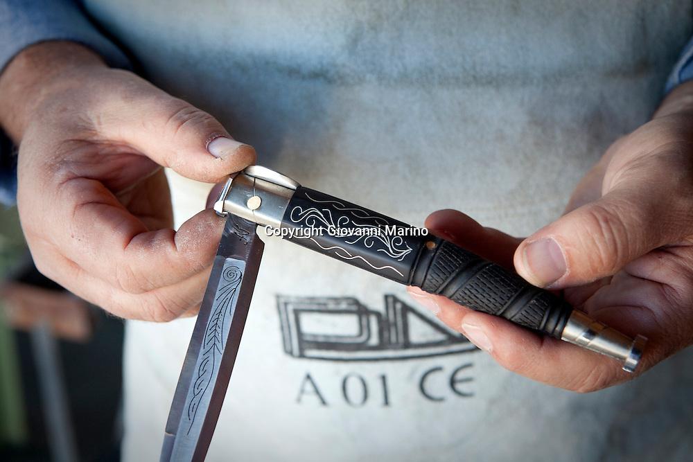 """Avigliano (PZ), 04-10-2010 ITALY - Vito Aquila, artigiano di Balestre. Il coltello di Avigliano, comunemente conosciuto come """"balestra"""", impreziosito con decorazioni in argento e ottone che le conferivano un certo valore non solo artistico,ha identificato per tutto l'Ottocento e parte del Novecento il carattere fiero e risoluto del popolo aviglianese, come attestato in una lunga casistica di riscontri documentari. La """"balestra"""" è un'arma a tutti gli effetti, ed è già considerata -nell'ambito delle manifatture di ferro - oggetto di pregio. Per l'approvvigionamento dell'argento e dell'ottone destinati alla decorazione del manico del coltello gli armieri si rivolgevano agli orefici o agli ottonari. La """"balestra"""" era un'arma del popolo, pronta ad essere impiegata, a seconda delle circostanze, per la difesa o l'offesa tanto dagli uomini quanto dalle donne. Queste, la ricevevano come regalo di fidanzamento dal rispettivo promesso sposo per meglio difendere il proprio onore, perpetrando un'usanza molto sentita almeno fino ai primi decenni del '900..Nella Foto: Particolare della molla esterna """"tre scrocchi""""."""