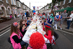 © Licensed to London News Pictures. 02/06/12. LONDON, UK. Children of Ravenscroft Road in Canning Town, East London sit at a table during a Jubilee street party held by local residents. The Royal Jubilee celebrations. Great Britain is celebrating the 60th  anniversary of the countries Monarch HRH Queen Elizabeth II accession to the throne this weekend Photo credit : LNP