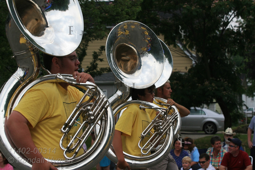 High school marching band tuba players march down residential street in annual Circus City Parade; Peru, Indiana.