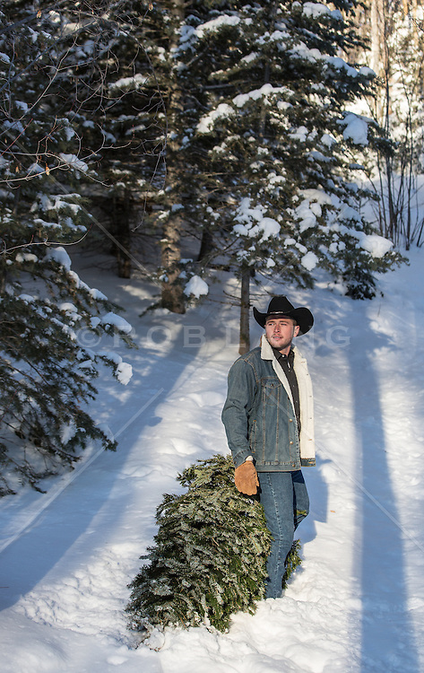 cowboy with a freshly cut Christmas tree in the snowy mountains