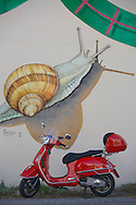 A red Vespa motor scooter is parked by a building exterior with a painted mural featuring a large snail along the Route Napoleon in southeastern France.