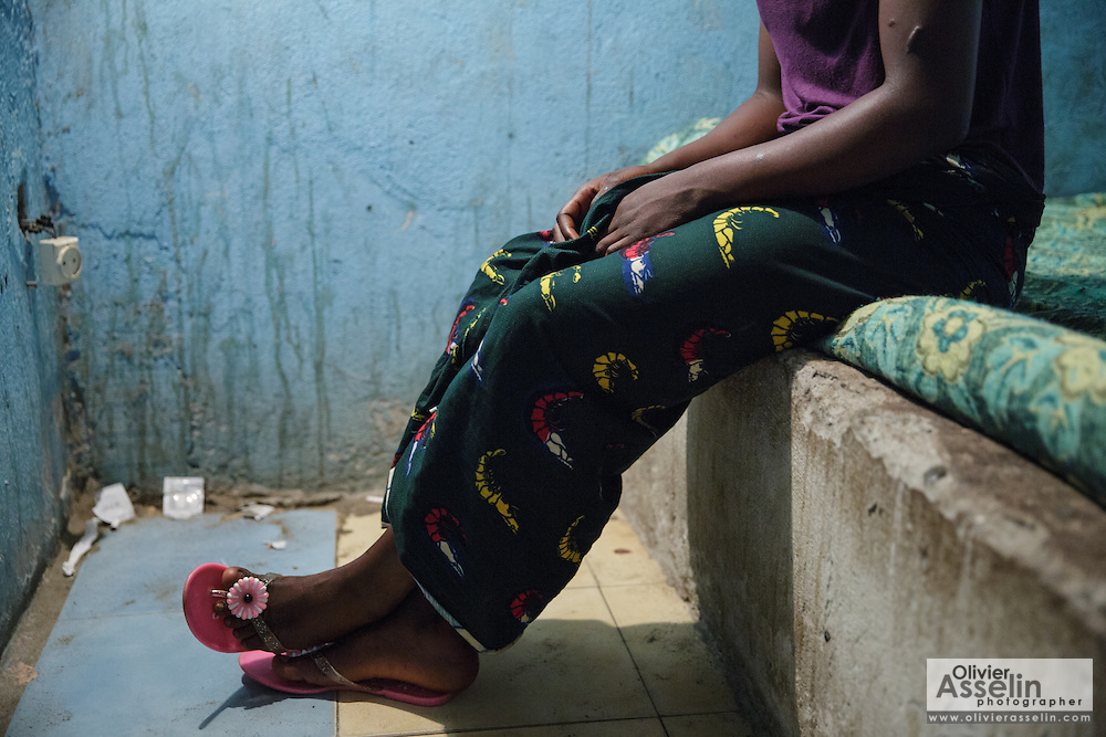 "Nicole, 16, sits in one of the rooms where she meets clients in a brothel in Abidjan, Cote d'Ivoire on Wednesday July 17, 2013. Nicole started working as a sex worker after running away from home, where her mother used to beat her. She says she can have up to 10 or 20 clients in a day; each of them pays 1000 CFA (2$). ""When I started I went for a whole week without using condoms. I was new, I didn't know"", she says. ""Sometimes the police come to catch us. We have to pay them 3000, 5000 or 10,000 so that they leave us alone. Other times you have to sleep with them."" Nicole went to school up to grade 5."