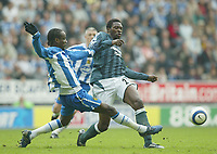 Photo: Aidan Ellis.<br /> Wigan Athletic v Newcastle United. The Barclays Premiership. 15/10/2005.<br /> Wigan's Pascal Chimbonda tackles Newcastle's Shola Ameobi