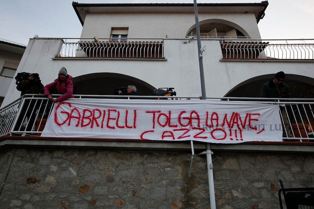"Residents hang a bang reading ""Gabrielli get rid of the fucking ship"" before a meeting for locals to discuss the situation following the shipwreck of the Costa Concordia off the west coast of Italy at Giglio island January 30, 2012. The banner refers to the Civil Protection agency chief Franco Gabrielli, who is in charge of the salvage operation, who said removing the massive wreck from its position outside the port could take up to a year...REUTERS/Darrin Zammit Lupi (ITALY)"