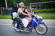 """Sept. 27, 2009 -- BACHO, THAILAND: Muslim Thai families use motorcycles for family transportation in Bacho, Narathiwat, Thailand. Thailand's three southern most provinces; Yala, Pattani and Narathiwat are often called """"restive"""" and a decades long Muslim insurgency has gained traction recently. Nearly 4,000 people have been killed since 2004. The three southern provinces are under emergency control and there are more than 60,000 Thai military, police and paramilitary militia forces trying to keep the peace battling insurgents who favor car bombs and assassination.   Photo by Jack Kurtz"""