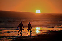 2 people walking through a sunset at the beach