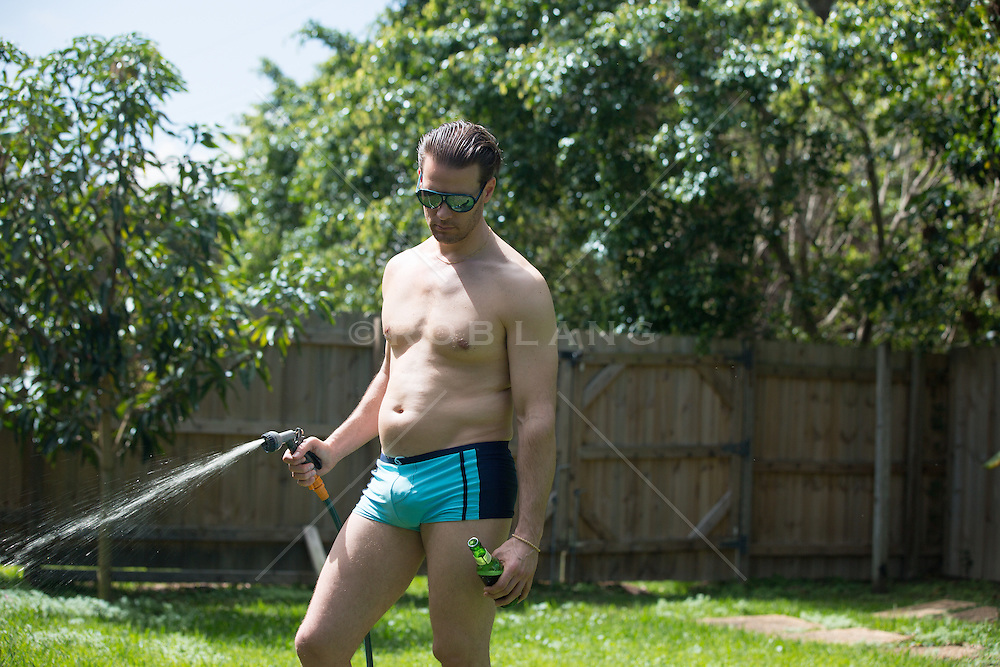 a slightly overweight man in a tight bathing suit watering his lawn while holding a beer in one hand