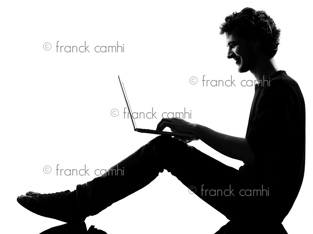 young man silhouette silhouette sitting computing computer laptop in studio isolated on white background