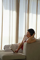 Woman reading book reclining on sofa