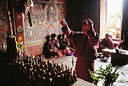 Inside the Shingkhey Buddhist Temple, a two-day ceremony is held to bless the village of Shingkhey, Bhutan. To a continuous background of chanting, the monks fill the valley with long, slow, deep notes from their horns. From Peter Menzel's Material World Project.