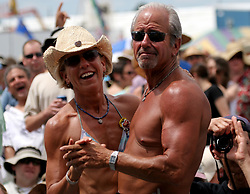30 April 2006. New Orleans, Louisiana. Jazzfest . <br /> The first New Orleans Jazz and Heritage festival following the disaster of Hurricane Katrina. Fans enjoy listening to legendary guitarist Sonny Landreth on the Acura stage.<br /> Photo ©Charlie Varley/varleypix.com<br /> All rights reserved.