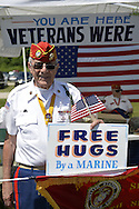 Old Westbury, New York. United States. 7th June 2015. Veteran JOHN GIORDANO, of Whitestone, holds a FREE HUGS By a MARINE sign at the fundraising booth of the Marine Corps League North Shore Queens Detachment #240 at the 50th Annual Spring Meet Car Show sponsored by Greater New York Region Antique Automobile Club of America. Over 1,000 antique, classic, and custom cars participated at the popular Long Island vintage car show held at historic Old Westbury Gardens.