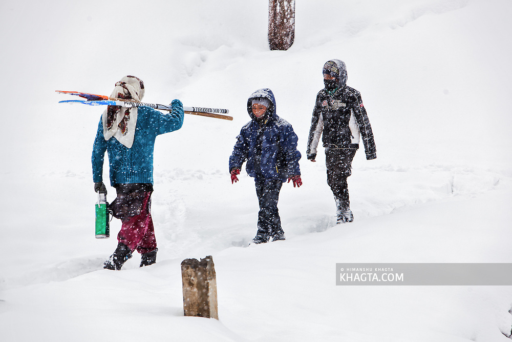 Lady carrying snow shovels passed two kids on a narrow path in Kaza on a winter in Spiti