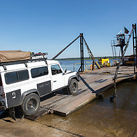 Africa, Zambia, Kazungula, Land Rover Defender safari truck drives onto ferry crossing Zambezi River toward Botswana