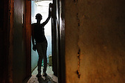 Lucie, 15, stands in the doorway of one of the rooms where she meets clients in a brothel in Abidjan, Cote d'Ivoire on Wednesday July 17, 2013. Lucie left her father's home in northwestern Cote d'Ivoire because she couldn't get along with his third wife. She would prefer working in home cleaning, but has no references and no one will hire her. She says she's had unprotected sex with clients only 3 times, at the client's request. On those occasions, she charged 2000 CFA (4$) instead of the usual 1000. Lucie has never been to school.