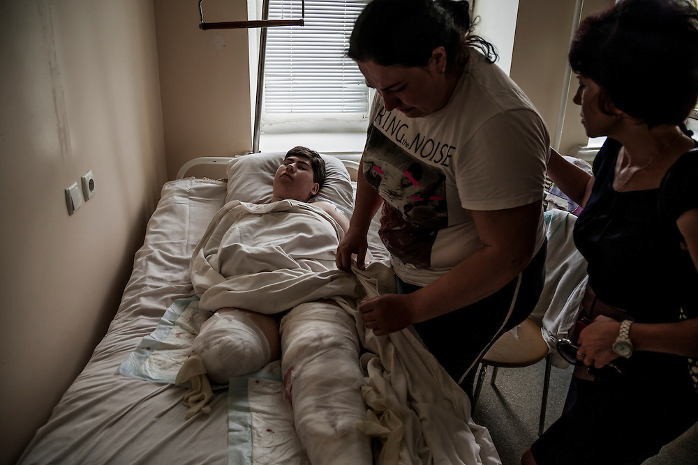 Svetlana, injured by shelling, lays on a bed as the sister Elena takes care of her at hospital in Donetsk.