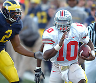 MORNING JOURNAL/DAVID RICHARD.Ohio State quarterback Troy Smith runs down the sideline for a first down as defender Shawn Crable gives chase.