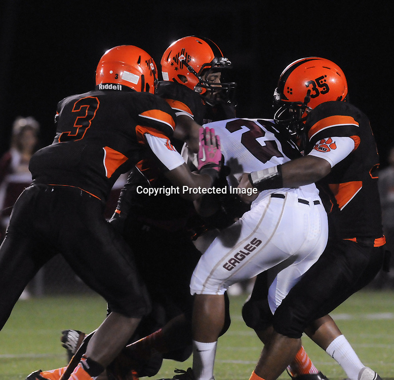 New Hanover High School's Nykheinma Walker, left, Dajourn Austin, center, and Anthony Barriner combine for a tackle on Ashley High School's Jylan Mack Friday October 10, 2014 at Legion Stadium in Wilmington, N.C. (Jason A. Frizzelle)