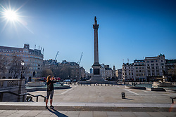 © Licensed to London News Pictures. 25/03/2020. London, UK. A women stops to take a picture of an empty Trafalgar Square while exercising during lockdown as Prime Minister Boris Johnson orders police to enforced the new rules. Prince Charles is confirmed to have contracted Covid19 as the crisis continues. Photo credit: Alex Lentati/LNP