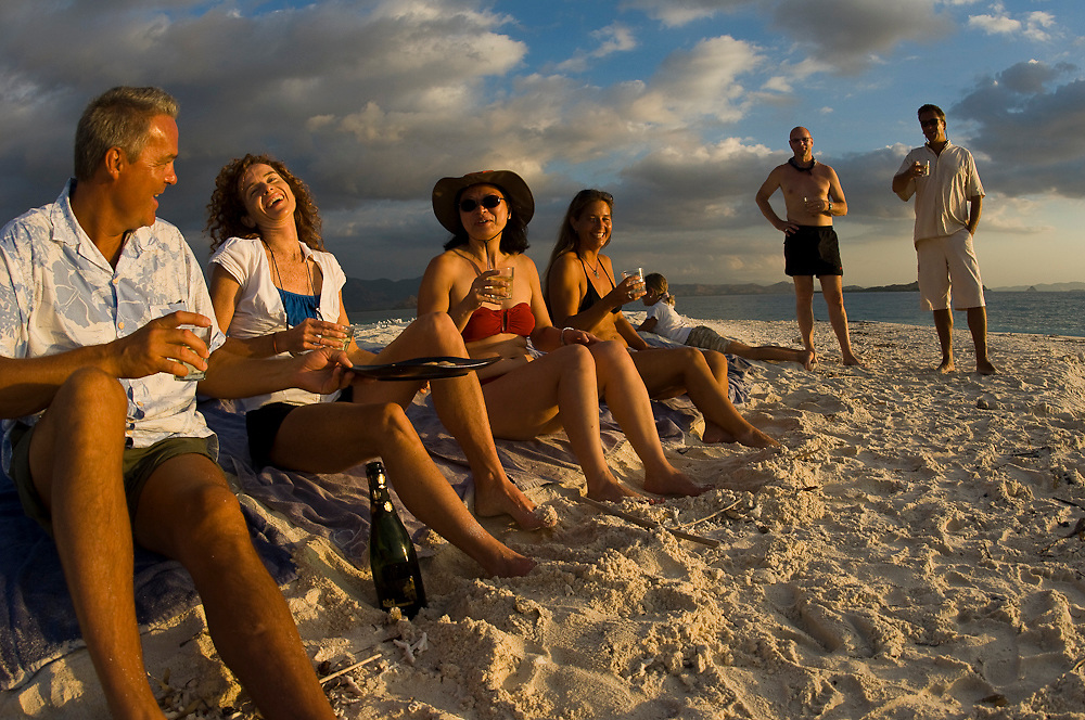 Tourists enjoy happy hour on a beach in Komodo National Park, Indonesia.