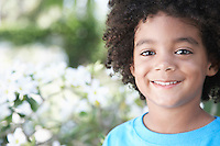 Boy (5-6 years) smiling outdoors portrait close-up