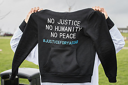 "© Licensed to London News Pictures. 06/01/2017. Huddersfield, UK. A man holds up a hoodie with "" No justice no humanity no peace #justiceforyassar"" at the funeral of Yassar Yaqub at Hey Lane Cemmetary in Huddersfield, West Yorkshire. Yaqub, 28, from Huddersfield, was shot dead in a car stopped near junction 24 of the M62 as part of a planned police operation. Photo credit: Joel Goodman/LNP"