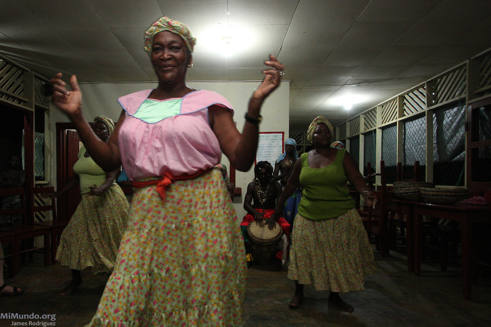 "Eulalia ""Lala"" Castillo, a Garífuna Uruga, or storyteller, dances Punta with her disciples from the Triunfo de la Cruz dance troop. Garifuna communities, descendants of shipwrecked would-be African slaves, have inhabited most of the Central American Atlantic coast for over 200 years. Since the mid 1990's, mega-tourism projects threaten the continuity of the communities and the UNESCO-declared world heritage Garifuna culture and language as well. Tela, Atlántida, Honduras, April 2009."