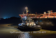 A tugboat assists a large vessel as it transits the Panama Canal at nighttime.