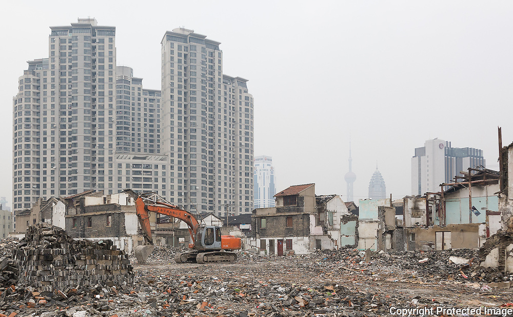 Vanishing Shanghai IV. An area of Hutongs or traditional low-rise housing sits between already demolished housing and new high rise developments behind. The Oriental Pearl TV Tower is viable in the distance. Shanghai, China, 2007