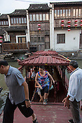 People disembark from a boat along Shantang canal in Suzhou, China.