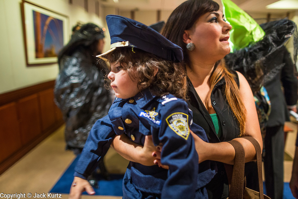 31 OCTOBER 2013 - PHOENIX, AZ:    A woman holds her son, dressed as a police officer, during an immigrants rights picket in the offices of Arizona Governor Jan Brewer in the foyer to her office Thursday. About 20 supporters of the DREAM Act and the deferred action program of President Barack Obama visited the office of Arizona Governor Jan Brewer to protest her decision to deny drivers licenses to Arizona DREAMERS and immigrants granted deferred action status by immigration authorities. The protest was a part of ongoing series of actions by immigration rights activists in Arizona to protest against anti-immigrant actions taken by Arizona political leaders.PHOTO BY JACK KURTZ