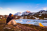 A man looking with binoculars from camp at Lost Lake at sunset. Resurrection Peaks in the background. Chugach National Forest, Kenai Peninsula, Southcentral Alaska, Spring.