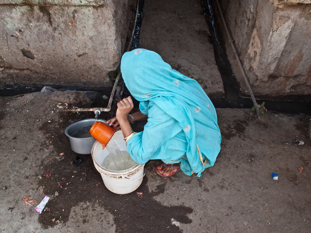 Gujarati woman in turquoise colored shawl pours water from a street spigot into her bucket.