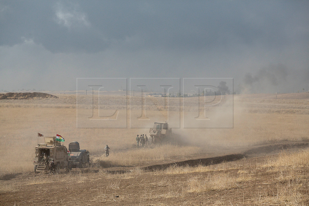 20/10/2016. Bashiqa, Iraq. Kurdish peshmerga engineers use an armoured bulldozer to clear a path as an Islamic State held village burns from coalition airstrikes during a large offensive to retake ISIS held areas near Bashiqa Iraq today (20/10/2016).<br /> <br /> Launched in the early hours of today with support from coalition special forces and air strikes, the attack is part of the larger operation to retake Mosul from the Islamic State, and involves both the Kurds and the Iraqi Army. The city of Bashiqa, around 9 miles north of Mosul, is one of several gateway areas that must be taken before any attempted offensive on Mosul itself.<br /> <br /> Despite the peshmerga suffering several casualties after militants fought back using mortars, heavy machine guns and snipers, the Kurdish forces were quickly taking ground with Haider al-Abadi, the Iraqi prime minister, stating that the operation to retake Mosul was progressing faster than expected. Photo credit: Matt Cetti-Roberts/LNP