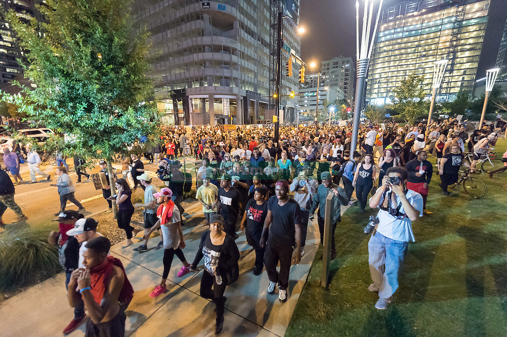 September 22, 2016 - Charlotte, North Carolina, United States of America - September 22, 2016 - Charlotte, NC, USA - Protestors make their way through Uptown during a third day of protests in Charlotte, North Carolina on Thursday, Sept. 22, 2016. This is the third day of protests that erupted after a police officer's fatal shooting of an African-American man Tuesday afternoon and the first full day of a declared State of Emergency by the governor. (Credit Image: © Sean Meyers via ZUMA Wire)