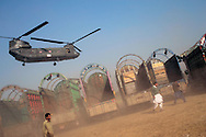 A US Army Chinook helicopter kicks up a spray of dust over Pakistani trucks waiting to be loaded with aid for delivery to earthquake affected regions, November 5, 2005, Rawalpindi, Pakistan. The South Asia earthquake measured 7.6 on the Richter Scale in Pakistan Administered Kashmir just before 9am on Saturday, October 8, 2005 and is the twelfth most destructive earthquake in recorded history, killing 87,000 and internally displacing 3 million. Early assessments indicate it will take upwards of 10 years for the affected regions to fully recover from the damage, however, scientists estimate the region should prepare for future earthquakes on a much larger scale, citing the Eurasian and Indian tectonic plates running through Kashmir as extremely  unstable. (Photo by Warrick Page)